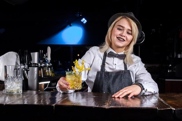 Garotas do barman fazendo um coquetel na brasserie