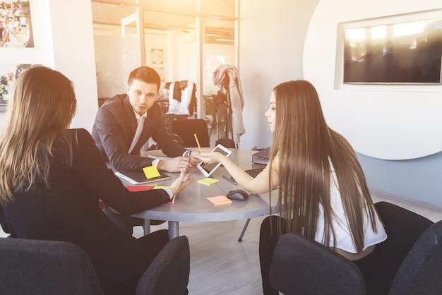 Garotas e um cara estão sentados à mesa e discutindo um plano de negócios, trabalho, escritório
