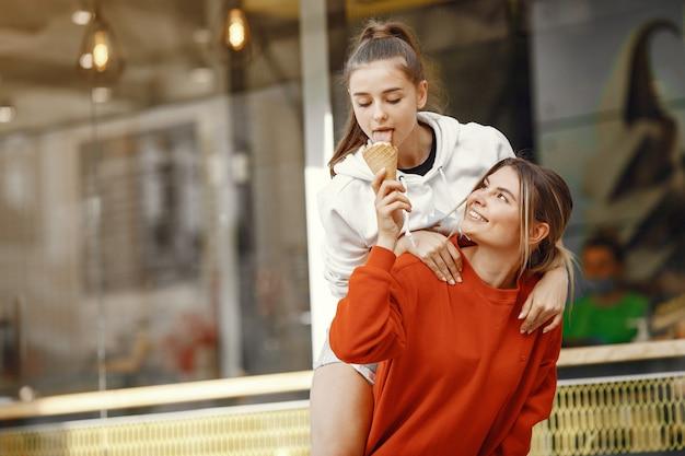 Garotas em uma cidade de verão com sorvete