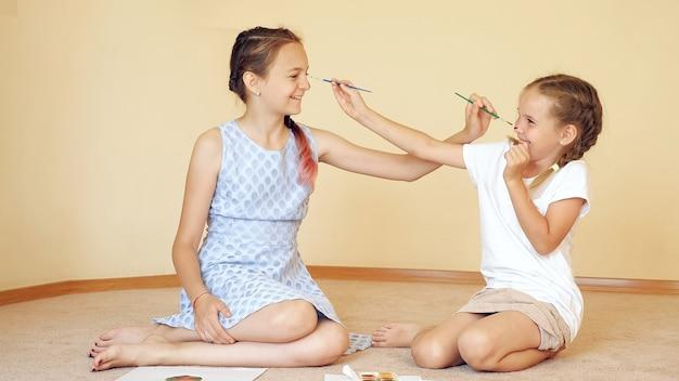 Garotas encantadoras sentadas no chão com papel e aquarela pintando o nariz uma para a outra se divertindo