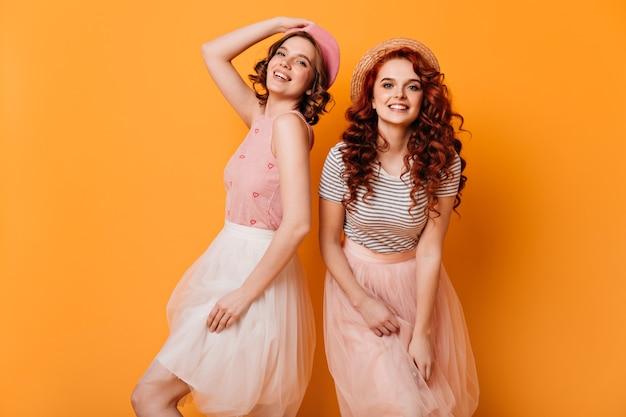Garotas encaracoladas em saias dançando sobre fundo amarelo. foto de estúdio de lindas senhoras caucasianos expressando felicidade.