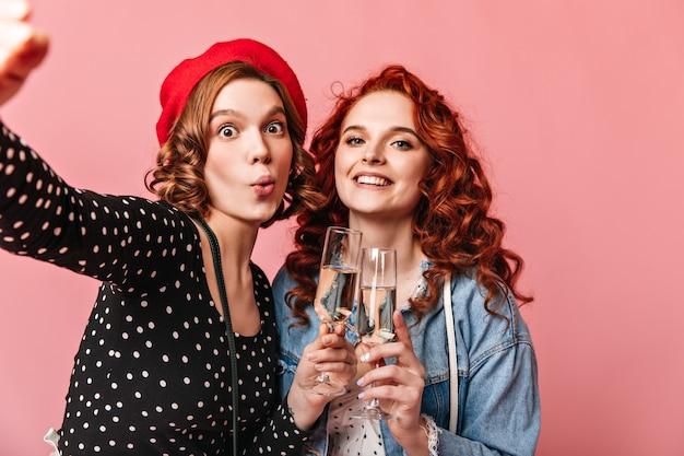 Garotas engraçadas com champanhe tomando selfie. duas melhores amigas, apreciando o evento e segurando um copo de vinho no fundo rosa.
