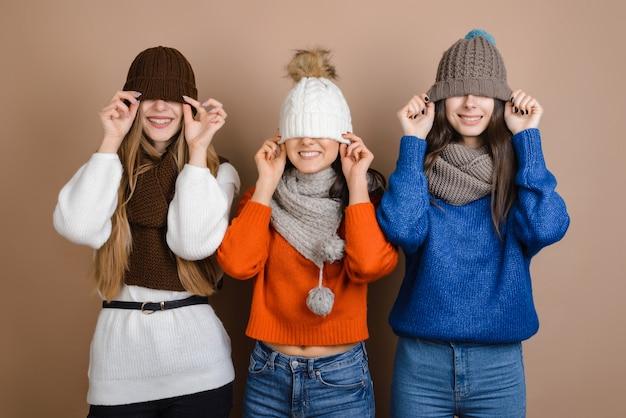 Garotas engraçadas com lenços puxavam os chapéus nos olhos
