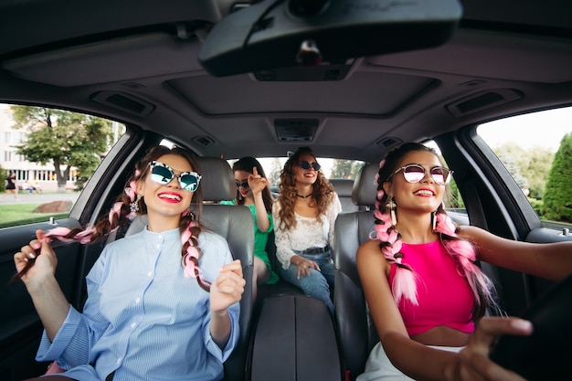 Garotas engraçadas com óculos de sol se divertem, andam de skate em um carro caro. rolando e cantando no carro em sua cidade natal no fim de semana.