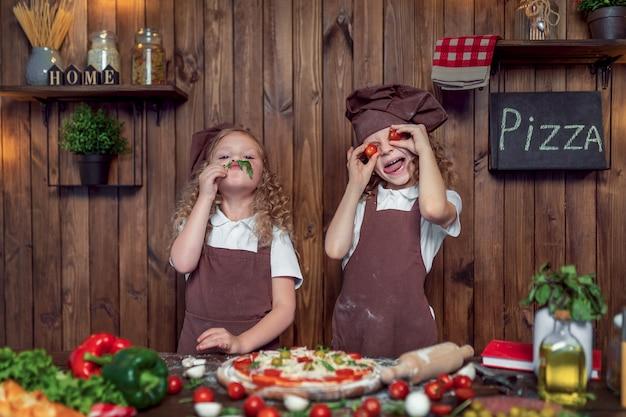 Garotas engraçadas cozinhar pizza e brincar com tomate e alface