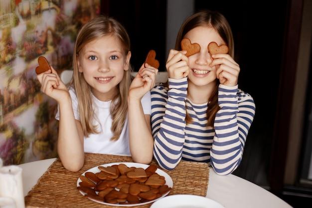 Garotas engraçadas e rindo seguram biscoitos em forma de coração, fecham os olhos e brincam