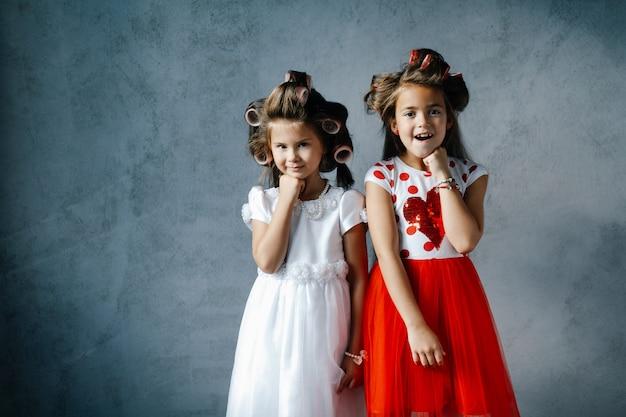 Garotas engraçadas em vestidos com rolos de cabelo posando contra a parede