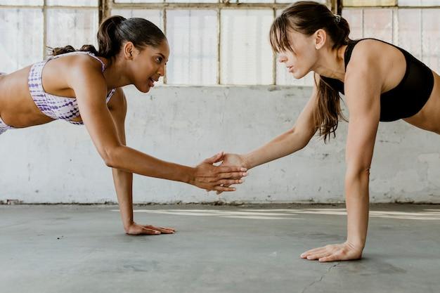 Garotas esportivas fazendo uma prancha juntas