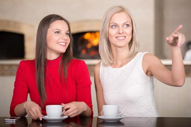 Garotas estão assistindo em algum lugar, sentadas na pizerria.