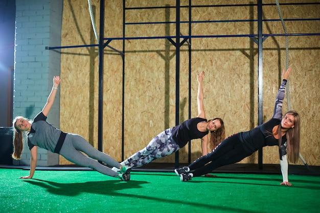 Garotas fazendo exercícios perto da parede no ginásio.