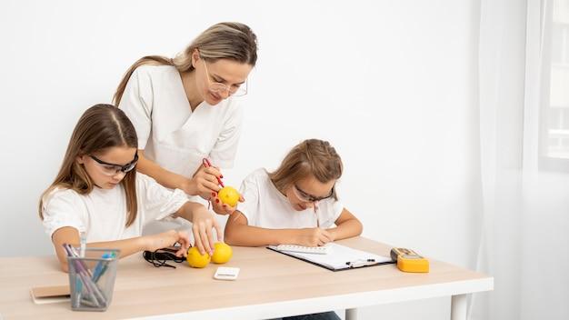 Garotas fazendo experimentos científicos com uma professora
