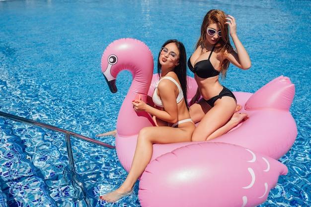 Garotas felizes com lindas figuras se divertindo em flamingos infláveis na piscina