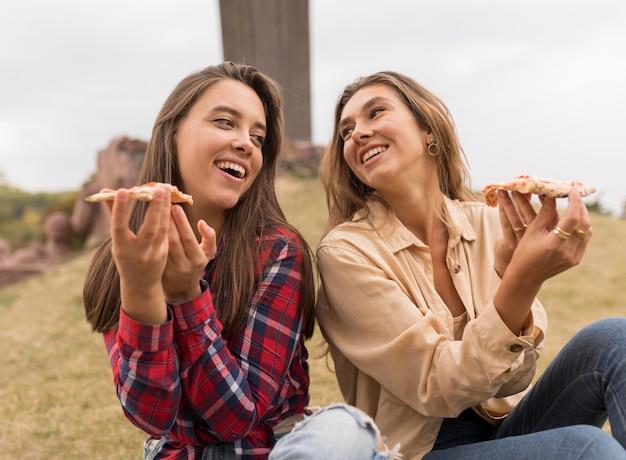 Garotas felizes comendo fatias de pizza ao ar livre
