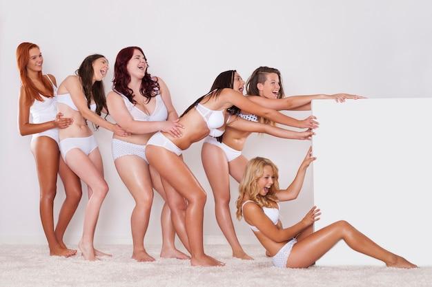 Garotas felizes de cueca puxando o quadro branco