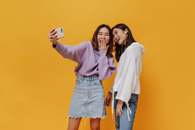 Garotas felizes em camisolas tiram selfie e riem na parede laranja
