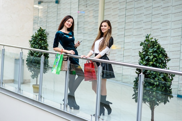 Garotas felizes estão fazendo compras no shopping.