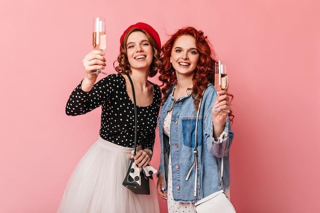 Garotas felizes levantando taças de vinho. vista frontal de amigos comemorando algo com champanhe.
