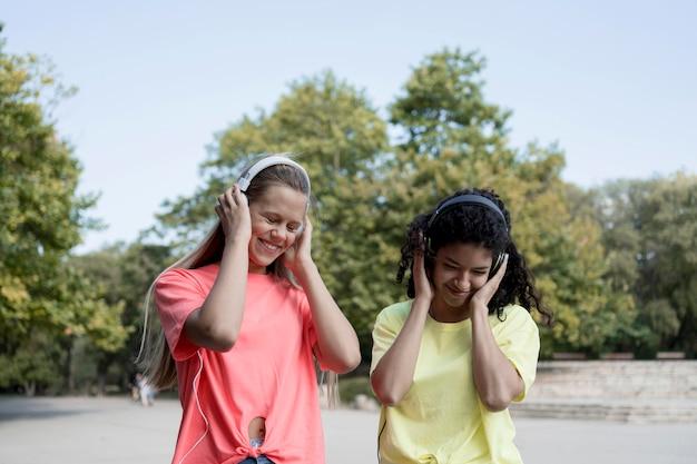 Garotas felizes usando fones de ouvido
