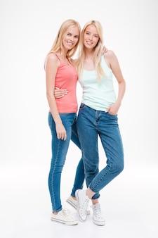 Garotas felizes vestidas com jeans e camisetas de formiga posando. isolado sobre a parede branca. olhando para a frente.