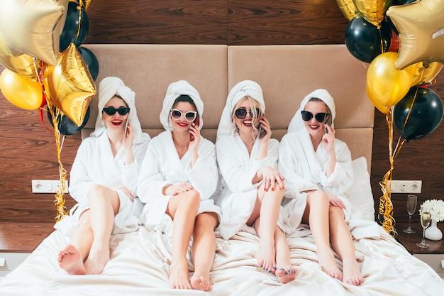 Garotas festeiras de roupão falando em smartphones. estilo de vida de lazer urbano das mulheres. óculos de sol e turbantes de toalha ligados