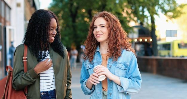 Garotas fofoqueiras. cintura para cima a vista do retrato das duas amigas multirraciais conversando e bebendo café enquanto caminhava na rua de verão. conceito de férias