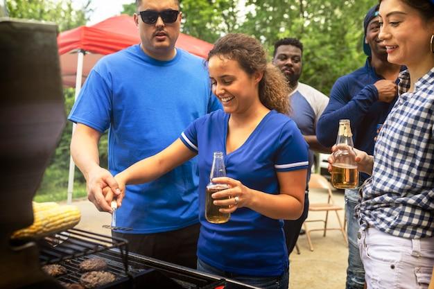 Garotas grelhando hambúrgueres em uma festa ao ar livre