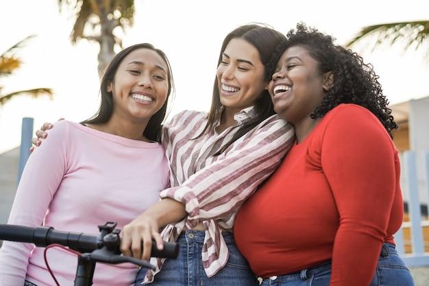 Garotas latinas felizes se divertindo com uma scooter elétrica ao ar livre na cidade - foco principal no olho da mulher africana