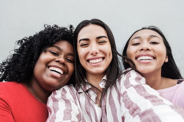Garotas latinas felizes se divertindo fazendo selfie juntas ao ar livre na cidade - foco principal no rosto da garota negra