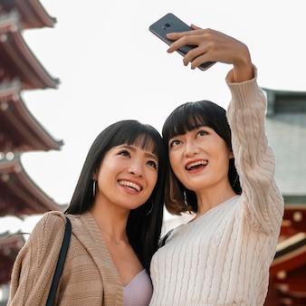 Garotas lindas asiáticas tirando uma selfie