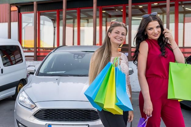 Garotas lindas com sacolas de compras no estacionamento