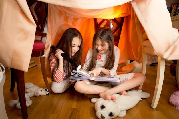 Garotas lindas e fofas lendo livro com lanterna em casa feita de cobertores