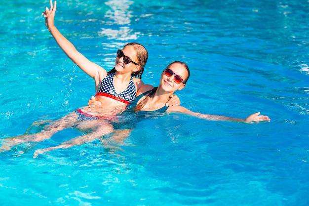Garotas lindas felizes se divertindo na piscina do resort