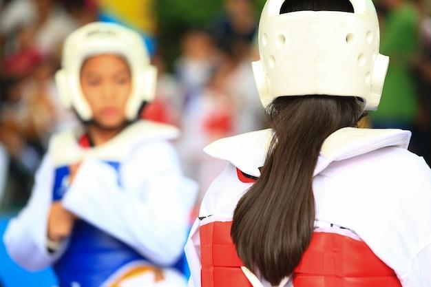 Garotas lutando no palco durante o torneio de taekwondo