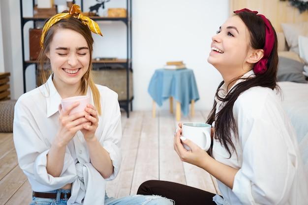 Garotas muito alegres se divertindo dentro de casa, sentadas no chão com canecas de café