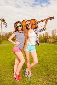Garotas muito sexy de chapéu e óculos andando no parque com violão