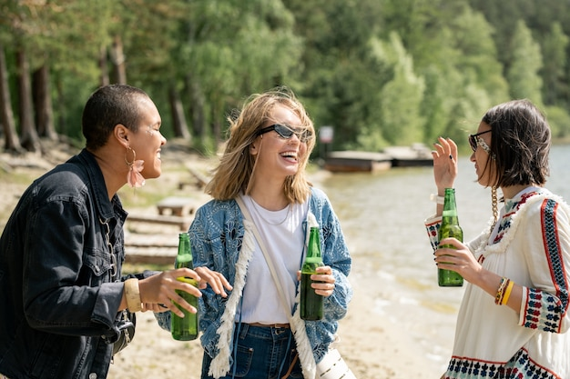 Garotas multiétnicas animadas bebendo cerveja e caminhando na praia em um centro recreativo