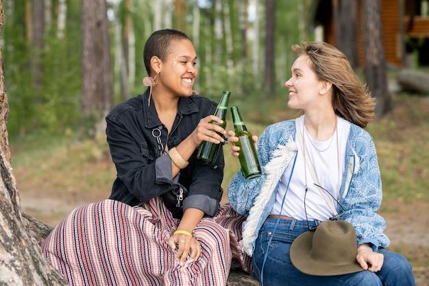 Garotas multiétnicas positivas sentadas na floresta tilintando garrafas enquanto bebem cerveja juntas no acampamento