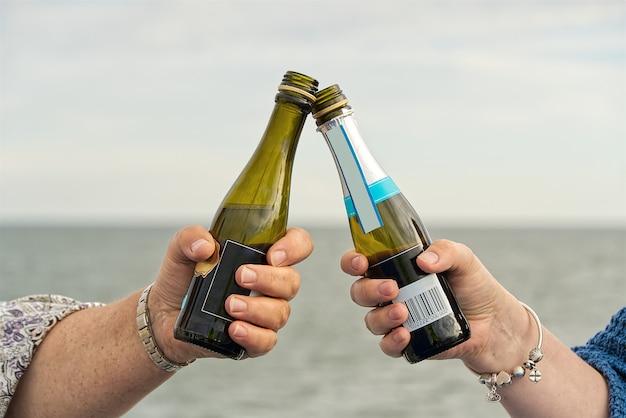 Garotas na balsa do cruzeiro tilintam taças de pequenas garrafas de champanhe enquanto viajam para o mar.