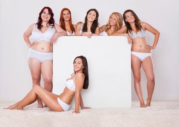 Garotas naturais posando com um quadro branco vazio