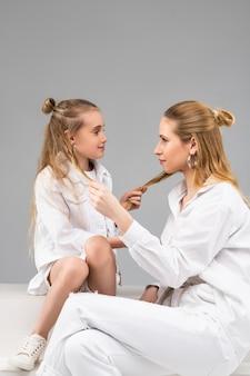 Garotas parecidas e bonitas de diferentes idades sentadas uma na frente da outra puxando mechas do cabelo