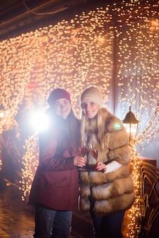 Garotas passando o tempo na festa de ano novo e desfrutando de champanhe. retrato ao ar livre de senhoras sobre fundo claro.