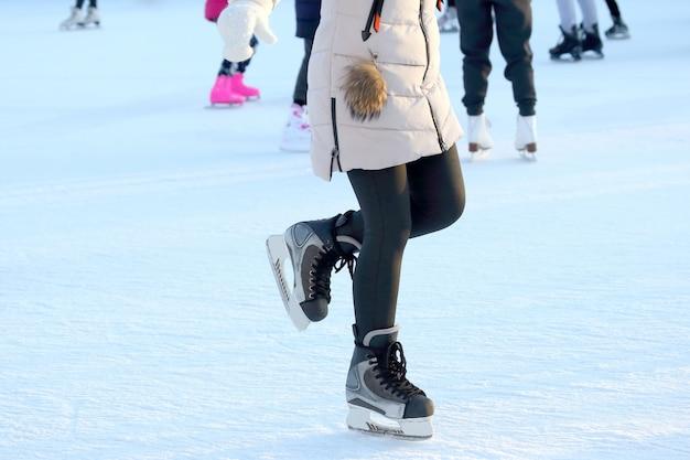 Garotas patinando de pés em patins na arena de gelo