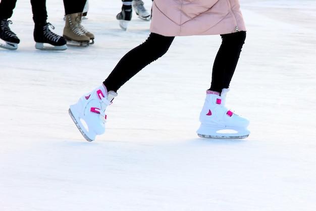 Garotas patinando no gelo a pé na pista de gelo