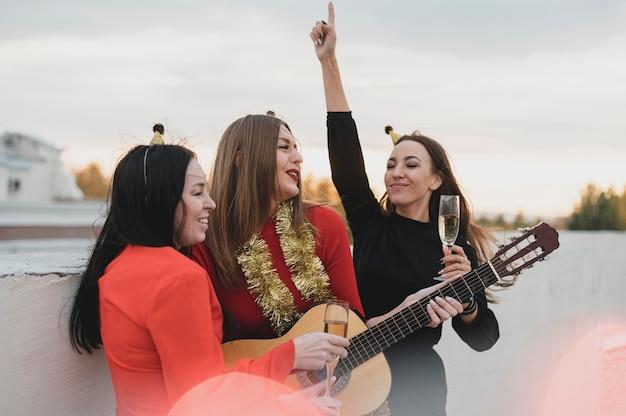 Garotas se divertindo com um violão na festa no terraço