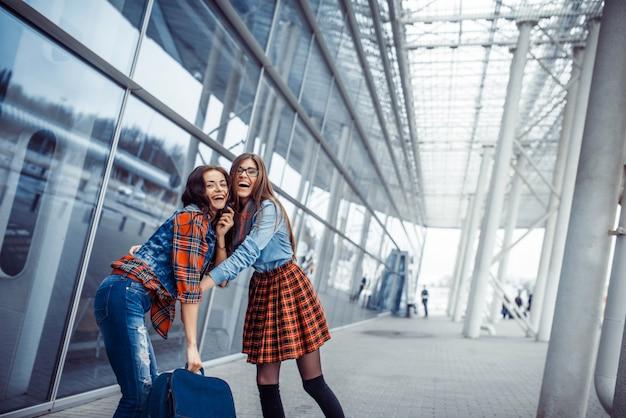 Garotas se divertindo e felizes quando se conheceram no aeroporto.