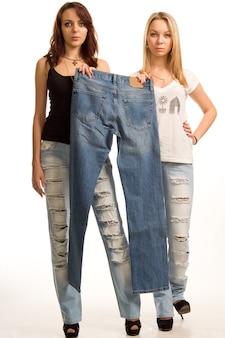 Garotas sensuais com expressões sensuais posando em jeans modernos segurando um par de jeans simples