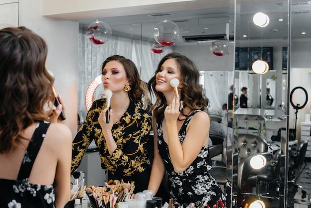Garotas sensuais se divertem e se maquiam para uma festa em frente ao espelho