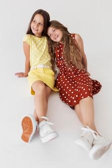 Garotas sorridentes com fotos completas usando vestidos