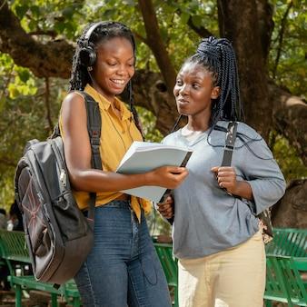 Garotas sorridentes de tiro médio com notebook