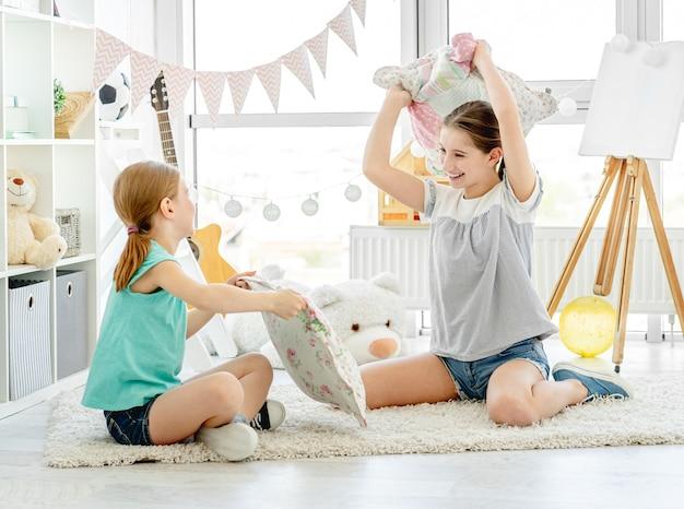 Garotas sorridentes lutando com almofadas no quarto das crianças